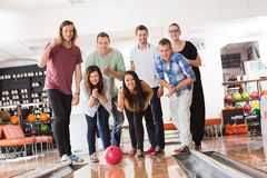 Woman Bowling While Friends Cheering in Club Royalty Free Stock Image
