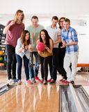 Woman Bowling While Friends Cheering Stock Images