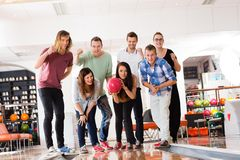 Woman Bowling While Friends Motivating in Club Royalty Free Stock Photo