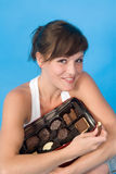 Woman with box of chocolates. Happy young woman with open box of chocolate biscuits, blue background Stock Images