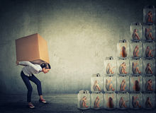 Woman with box climbing up a stair made of jars with women inside. Young woman with big box on her back climbing up steps made of jars with captive woman trapped royalty free stock photo