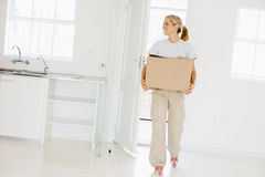 Woman with box moving into new home smiling.  Stock Photography