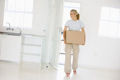 Woman with box moving into new home smiling.  Royalty Free Stock Images