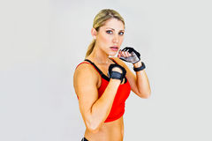 Woman boxer, aggressive and looks at the camera Royalty Free Stock Photos