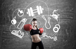 Woman boxer near blackboard with sport icons Stock Image