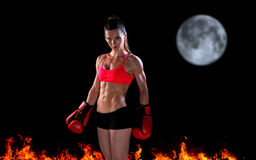 Woman boxer in night scene with fire and moon Royalty Free Stock Photography