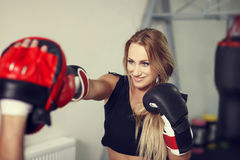 Woman boxer preparing in gym with instructor Royalty Free Stock Image