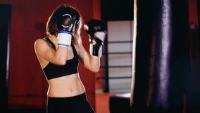 Woman boxer training in gym, boxing punching bag. 4K stock footage