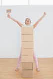Woman with boxes and paintbrush raising hands in new house Royalty Free Stock Photo