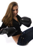 Woman boxing. Portrait of a young woman wearing boxing gloves against a white background Royalty Free Stock Photo