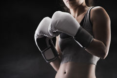 Woman boxing. Woman boxer, focus on boxing glove, shallow deep of field Royalty Free Stock Photo