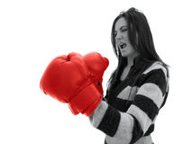 Woman with boxing gloves. Angry looking young woman wearing large red boxing gloves stock image