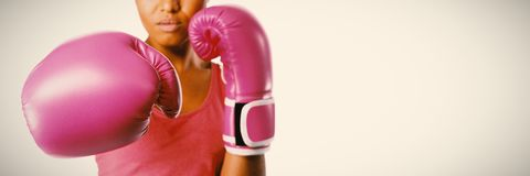 Woman fighting for breast cancer awareness. Woman with boxing gloves for breast cancer awareness on white background stock image