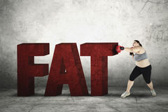 Woman with boxing gloves and fat word Royalty Free Stock Photography