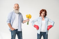 Woman in boxing gloves and husband with bouquet. Dissatisfied mature women in boxing gloves and her husband with bouquet, isolated on white Royalty Free Stock Photos