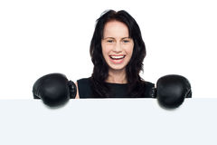 Woman with boxing gloves on posing behind billboard Royalty Free Stock Photography