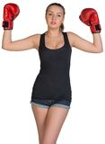 Woman in boxing gloves posing with her arms up Stock Photography