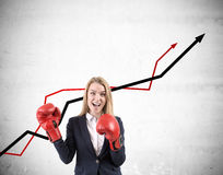 Woman with boxing gloves and red and black graphs Royalty Free Stock Photography
