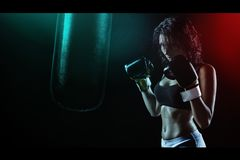Woman in Boxing Gloves With Sports Bra Posing Boxing Style in Front of Punching Bag Stock Photo