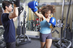 Woman boxing training. African American woman has a boxing workout with an Asian man Royalty Free Stock Photos