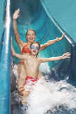 Woman And Boy With Arms Outstretched On Water Slide Stock Photography