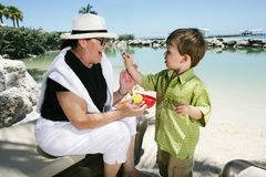 Woman and boy on beach. Woman and little boy play on the shore of a tropical beach Royalty Free Stock Image