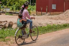 Woman and boy on bicycle in Cambodian countryside in Angkor Arch royalty free stock photos