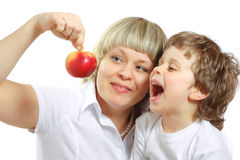 Woman and boy eating apple Stock Photos