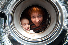 Woman and boy peer into get  washer Stock Photos