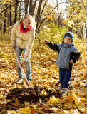 Woman and boy  planting  tree in autumn. Women and boy with spade outdoors planting  tree in autumn Stock Photo