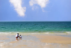 Woman and boy play on the beach with blue sea and clear sky. Family vacation Royalty Free Stock Images