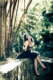 Woman in bra and heels sitting under bamboos. Young woman in bra and heels sitting under bamboos Stock Images