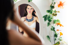 Woman in bra looking in mirror Stock Photo