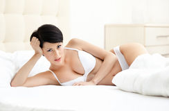 Woman in bra is lying in the bedstead Stock Images