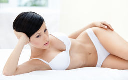 Woman in bra is lying in the comfortable bed Royalty Free Stock Photography
