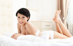 Woman in bra is lying in the queensize bed Royalty Free Stock Images