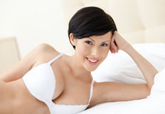 Woman in bra is lying in the spacious bed Royalty Free Stock Photography