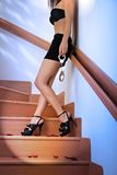 Woman in bra and mini skirt holding handcuffs. Woman in bra and mini skirt standing at stairway, holding handcuffs Stock Photos