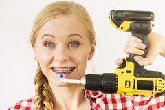 Woman with braces brushing teeth with drill. Funny teenage woman wearing braces holding drill about to brush her teeth stock images