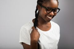 Woman With Braided Hair Wearing Eyeglasses Over Gray Background Royalty Free Stock Photos