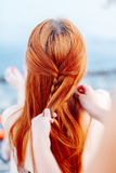 Woman braiding girl on beach. Anonymous woman standing behind redhead girl and braiding her hair on beach in sunlight Royalty Free Stock Photography