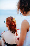 Woman braiding girl on beach. Anonymous woman standing behind redhead girl and braiding her hair on beach in sunlight Stock Photos