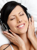 Woman in brassiere listens to music Stock Photography