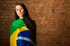 Woman in the Brazilian flag. On the background of a brick wall Royalty Free Stock Photos