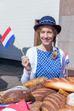 Woman with breads waving with dutch flag stock photos