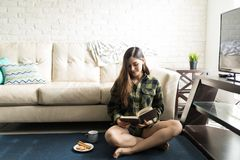 Woman With Breakfast And Book At Home. Full length of hippie woman in casual shirt reading book at home royalty free stock photo