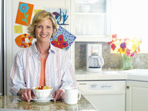 Woman with breakfast bowl and mug in kitchen, smiling, portrait Stock Photography
