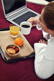 Woman breakfast in her bed with computer Royalty Free Stock Photo