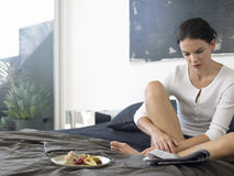 Woman With Breakfast Reading Newspaper On Bed Stock Photography