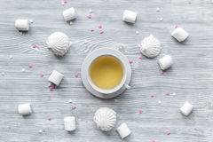 Woman breakfast with tea and marsh-mallow light wooden table top view pattern Stock Image